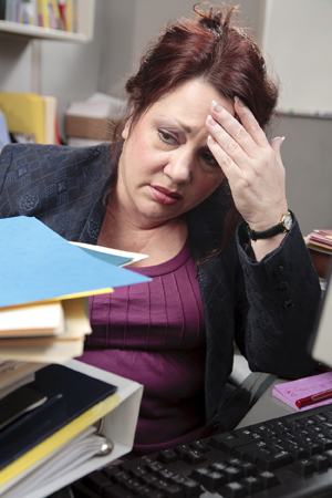 Overweight woman in an office cubicle behind a stack of folders and papers, holding head, under stress.