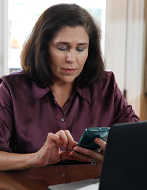 Woman talking on cell phone in front of laptop at home.