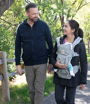 Woman with baby in front carrier walking with man outdoors.